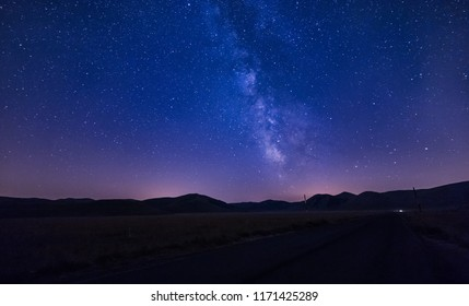 deep night sky stars with milky way over mountains. Italy. Castelluccio
