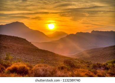 Deep orange Sunset behind the mountains.