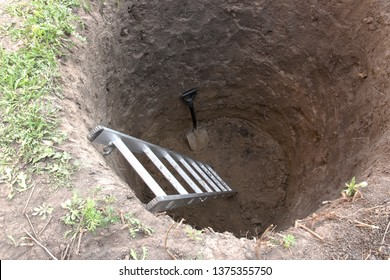 Deep pit in the ground. In the pit shovel and ladder. Digging a hole.