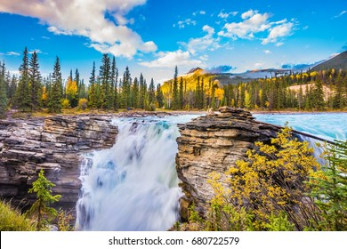 The deep raging falls of Athabasca.  The concept of extreme and ecological tourism. Clear autumn evening in Jasper National Park. Cold blue water at sunset
