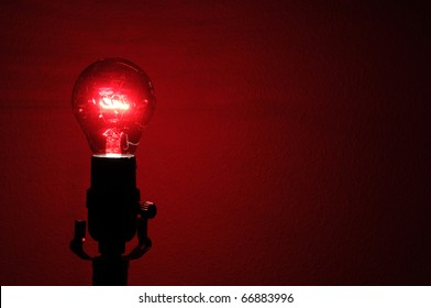 A deep red, almost infrared light bulb against a wall with copyspace on the right.