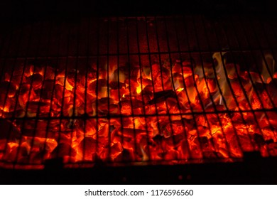Deep red charcoal on a grill slowly burning out