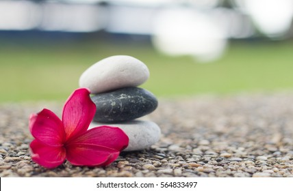 Deep red plumeria flower with stack of spa zen stones. Natural lighting and setting.