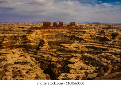 The deep red rock of the chocolate drops formation stands out prominently, as it overlooks the opposite side of the Maze Overlook abyss, in the Canyonlands National Park in Utah.