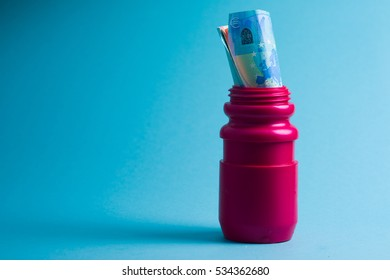 Deep red sporty water bottle with a euro note over a blue background. Concept for doping or corruption in sport.