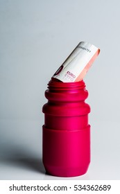Deep red sporty water bottle with a euro note over a white background. Concept for doping or corruption in sport.