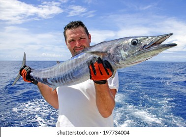 Deep sea fishing. Fisherman holding a wahoo fish.