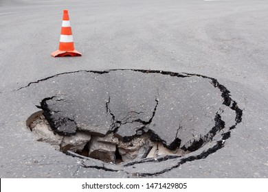 Deep sinkhole on a street city and orange traffic cone. Dangerous hole in the asphalt highway. Road with cracks. Bad construction. Damaged asphalt road collapse and fallen.  - Shutterstock ID 1471429805
