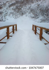 Deep snow covered wood beam footbridge on snowshoe and hiking trail in Winter.