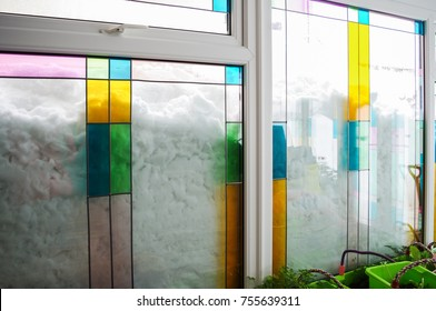 Deep snow piled high against stained glass windows, Inside looking out at the avalanche of snow.