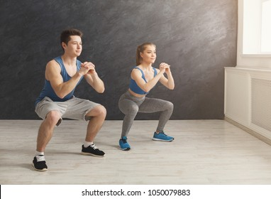 Deep squat. Fitness couple in sportswear doing squat exercises at gym, copy space