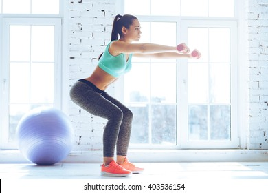 Deep squat. Side view of young beautiful woman in sportswear doing squat and holding dumbbells while standing in front of window at gym