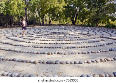 In deep thought, a woman walks a forest labyrinth