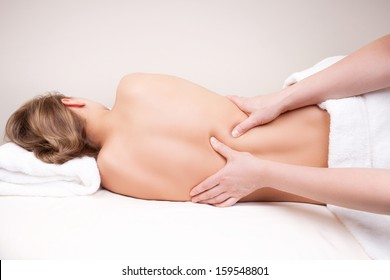 Deep tissue massage on the woman's middle back on erector spinae muscles