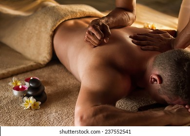 Deep tissue massage. Spa setup - stones, frangipani flowers and towels.