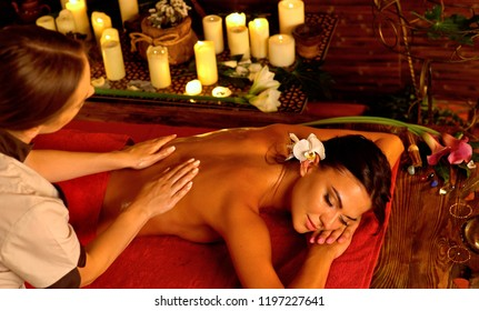 Deep tissue massage treatment in Ayurveda of woman in spa salon. Girl on candles background treats problem back. Luxary therapy interior with working masseuse.