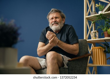 Deep torment. Old bearded man sitting on the chair, suffering from pain in the wrist on blue background. Concept of illness, diseases of the joints and bones, surgical pathology, healthcare.