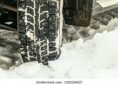 Deep tread of winter studded tires. Car wheel on a snowy winter road.