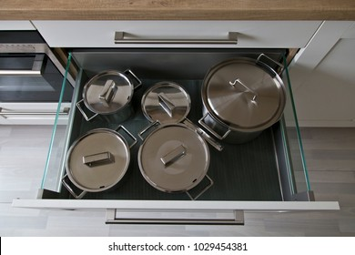 Deep white open kitchen drawer filled with stainless steel pans.
