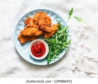 Deep-fried bread crumbs fried chicken fillet with ketchup and salad - delicious appetizer, tapas on white background, top view
