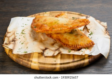 deep-fried pasties with pork and beef. piroshki with meat and herbs on a wooden board