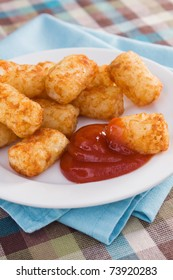 Deep-fried tater tots served with ketchup.