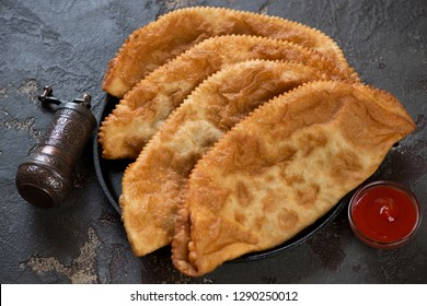 Deep-fried turnovers with minced meat and onion called chebureki, studio shot on a brown stone background