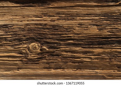 a deeply textured weathered old wooden board with with a single knot breaking the pattern