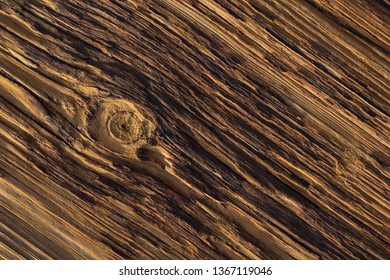 a deeply weathered textured old wooden board with with a single knot breaking the pattern