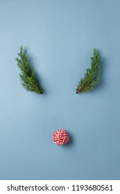 Deer face made of clew of candy cane Christmas rope and evergreen branches on blue background.