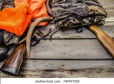 Deer Hunter Background. Antlers, ammunition, guns, hunter orange hat and rifles on a rustic wood background with copy space.
