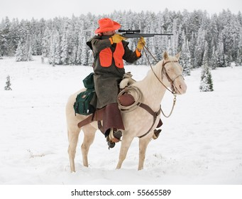 deer hunter riding white horse in snow aiming rifle