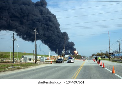 Deer Park, Texas / United States - March 19, 2019:Police restrict traffic around burning tanks. A massive plume of black smoke hangs over Houston
