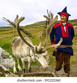 Deer and reindeer breeder dressed in national clothes the Sami in Honningsvag, Norway. The Sami are the people inhabiting the Arctic