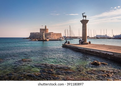 Deer statue at Mandraki Harbour, Rhodes island, Greece. On the background the fortress of st. Nicholas.
