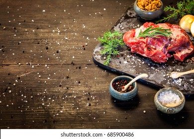 Deer or venison roast, traditional finnish food, rosvopaisti, with Chanterelle fungus, Sea salt, red, green, white pepper and coriander in clay pots on an old black rustic table.
