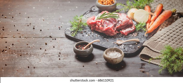 Deer or venison roast, traditional finnish food, rosvopaisti, with Chanterelle fungus, Sea salt, red, white pepper and coriander in clay pots on an old black rustic table. Banner, copy space, tunning