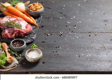 Deer or venison roast with vegetables, sea salt, red, green, white pepper and coriander in clay pots on an old black rustic table. Soup or stew preparation. Copy space