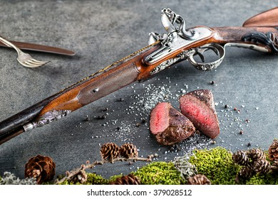 deer or venison steak with antique long gun, cutlery and ingredients like sea salt and pepper, food background for restaurant or hunting loving