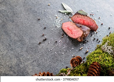 deer or venison steak with ingredients like sea salt, herbs and pepper, food background for restaurant or hunting loving