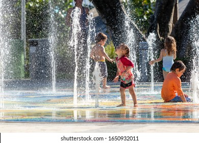 Deerfield Beach, FL / USA - 2/17/2020: Children in bathing suit playing in the splash pad water fountain in the sun at Sullivan Park in Florida with mothers and parental guardians nearby watching.