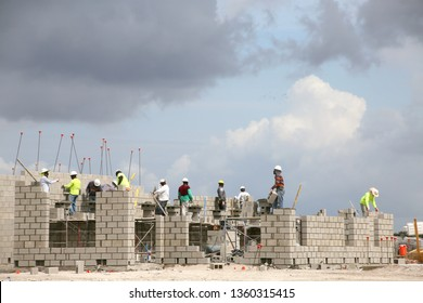 DEERFIELD BEACH, FLORIDA / USA - APRIL 5 2019:  Construction workers build the brick cement block inner skeleton foundation of a home near Crystal Lake Drive in a cloudy morning.