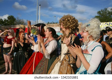 DEERFIELD BEACH, FLORIDA / USA - MARCH 9 2019:  Ladies in period costumes, hair and makeup applaud and cheer in reaction to a joust victory at the South Florida Renaissance Festival.