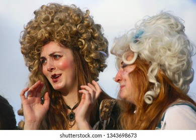 DEERFIELD BEACH, FLORIDA / USA - MARCH 9 2019:  Two young ladies in period dress, wigs and makeup react next to the action at a jousting match at the South Florida Renaissance Festival.