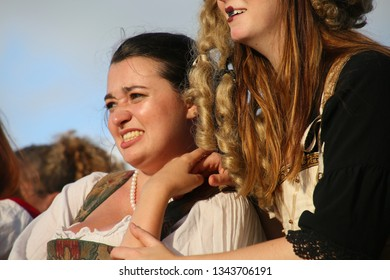 DEERFIELD BEACH, FLORIDA / USA - MARCH 9 2019:  Young lady in period dress and brown hair grimaces next to a violent jousting match at the South Florida Renaissance Festival.