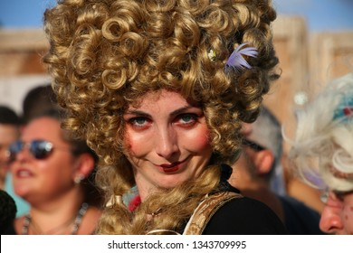 DEERFIELD BEACH, FLORIDA / USA - MARCH 9 2019:  Young woman wearing a reddish blonde wig and garish stripe of lipstick poses next to the jousting field match at the South Florida Renaissance Festival.