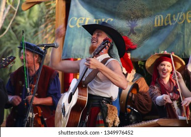 DEERFIELD BEACH, FLORIDA / USA - MARCH 9 2019:  The lead singer and guitar player of Celtic Mayhem finishes a song in a flourish of notes in the setting sun at the South Florida Renaissance Festival.