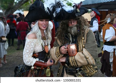 DEERFIELD BEACH, FLORIDA / USA - MARCH 9 2019:  Female and male pirates pose in black hats and period costumes with leather at dusk at the South Florida Renaissance Festival.