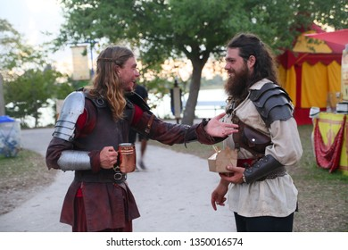DEERFIELD BEACH, FLORIDA / USA - MARCH 9 2019:  Two medieval knights in full costume socialize after a jousting match with drink and food in sunset at the South Florida Renaissance Festival.