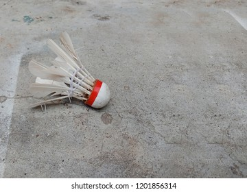 defeat badminton feathers broken shuttlecock and depression on cement texture